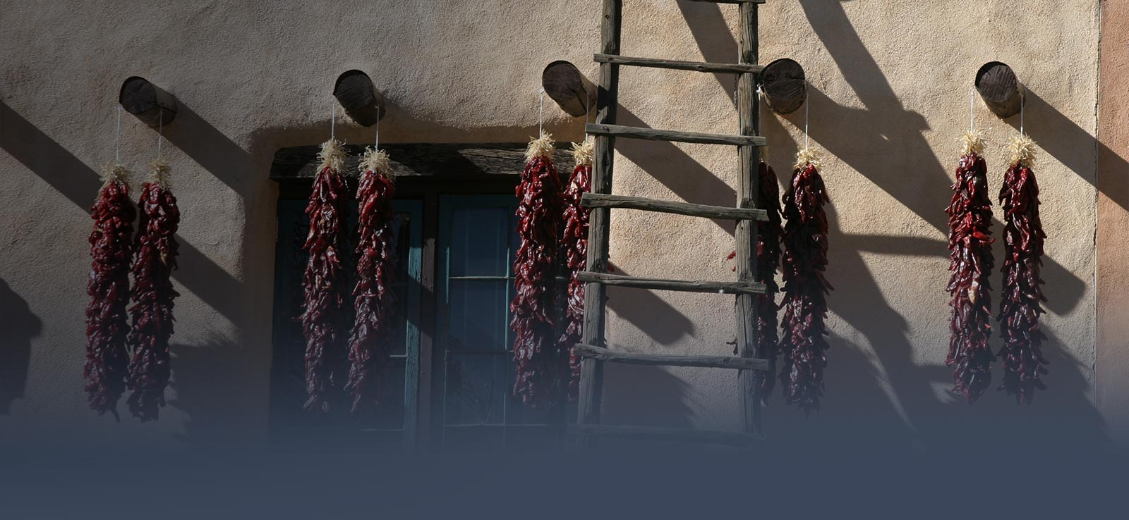 Ristras hanging from adobe house posts